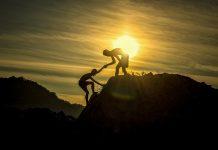 Twee personen beklimmen heuvel