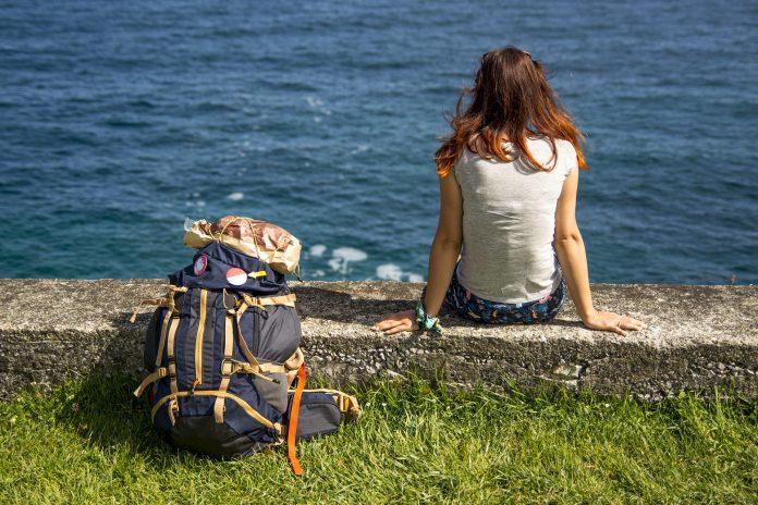 reiziger met rugzak bij het water