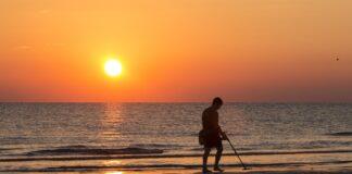 Iemand met metaaldetector op het strand