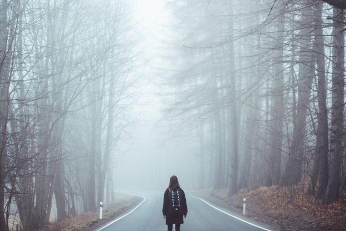 Meisje met rugzak op weg in de mist