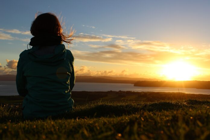 Persoon kijkt naar ondergaande zon