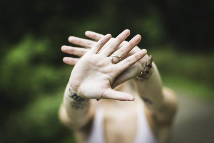 Meisje verbergt gezicht achter handen